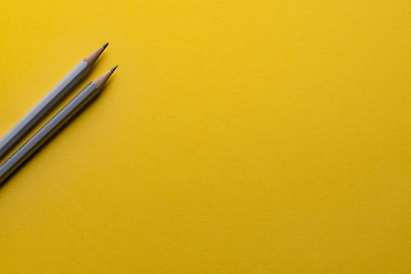 Two gray pencils on a bright yellow background